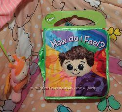 Развивающая игрушка первый подарок мягкая книжка How Do I Feel от Lamaze